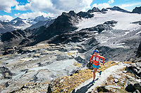 A woman trail running above the Cabane de Prafleuri while on the Via Valais, a multi-day trail running tour connecting Verbier with Zermatt, Switzerland.