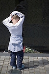 A young boy with arms on head stands in front of the Vietnam memorial in Washington D.C. in the United States.