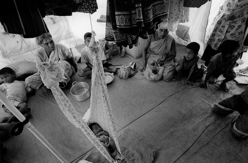 Tamil IDPs displaced by government shelling in Batticaloa District sit in a tent at an IDP camp in Batticaloa, Sri Lanka, Sunday, Mar. 11, 2007. The number of IDPs in Batticaloa surged to over 200,000 in March due to intense shelling by the Sri Lankan military in the districts surrounding Batticaloa. To make room for the latest influx of IDPs, the Sri Lanka Military began forcibly resettling IDPs to Vakharai and Kiliveddi where there is still very little support from relief agencies.