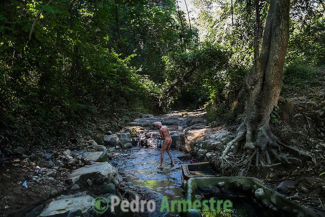 November 09, 2014. &quot;Water it&acute;s the real thing&quot;<br /> Felipe Ruiz, 65 years old, washes himself in a place called El Caballo with contaminated water. He doesn&rsquo; t have water at home and he has to walk near two hours to El Caballo. The people of Nejapa in El Salvador, have no drinking water because the Coca -Cola company overexploited the aquifer in the area, the most important source of water in this Central American country. This means that the population has to walk for hours to get water from wells and rivers. The problem is that these rivers and wells are contaminated by discharges that makes Coca- Cola and other factories that are installed in the area. The problem can increase: Coca Cola company has expansion plans, something that communities and NGOs want to stop. To make a liter of Coca Cola are needed 2,4 liters of water. &copy;Calamar2/ Pedro ARMESTRE