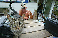 "Lifelong resident on the St. Johns River Stanley Oglesby, 70, visits a cat who adopted him on his houseboat at Rod and Siivi's Fish Camp in Geneva, Florida Thursday May 15, 2003. Oglesby, who lives at the camp on his houseboat, was born on the river and has stayed his entire life living on the river, saying, ""the river is the only way of life for me, I don't want to live anywhere else"".(Kelly Jordan)"