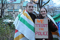 November 23, 2011, Toronto Police in significant numbers deployed during the predawn hours this morning, beginning the process of evicting the Occupy Toronto tent camp from St. James Park.  Here at first light of dawn, two unidentified protest supporters embrace holding a placard expressing trust in the police.