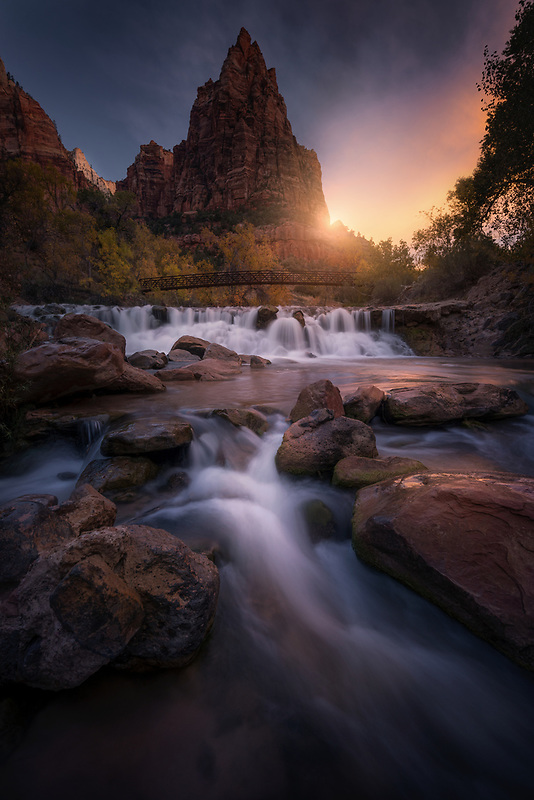 Golden sunrise illuminating rocky waterfalls. Zion National Park, UT