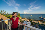 10 July 2013: SCUBA diver Sally Herschorn looks over the balcony at the penthouse level of Cobalt Coast Resort in West Bay, Grand Cayman Island. Located in the British West Indies in the  Caribbean, the Cayman Islands are renowned for excellent scuba diving, snorkeling, beaches and banking.  Mandatory Credit: Ed Wolfstein Photo *** RAW (NEF) Image File Available ***