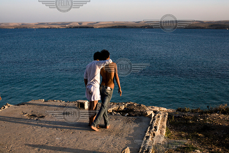 Two young men standing on the shore along the Mediterranean coast. On 17 February 2011 Libya saw the beginnings of a revolution against the 41 year regime of Col Muammar Gaddafi.