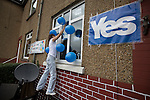 Pro-Scottish independence supporter Ann Shields attaching balloons to her house in Cardonald, Glasgow on the day of the independence referendum. Yes Scotland were campaigning for the country to leave the United Kingdom, whilst Better Together were campaigning for Scotland to remain in the UK. On the 18th of September 2014, the people of Scotland voted in a referendum to decide whether the country's union with England should continue or Scotland should become an independent nation once again and leave the United Kingdom.