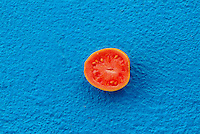 Close up of a pink guava fruit cut in half on blue background