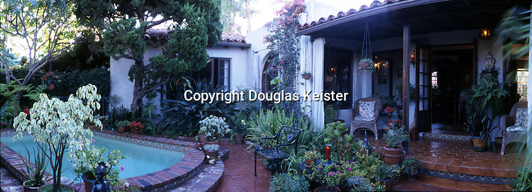This courtyard in San Diego is behind a 1926 Spanish Colonial Revival house designed by renowned architect Richard S. Requa. Requa was so enamored with Spanish architecture that he wrote a book in 1929 titled Old World Inspiration for American Architecture. One of the chapters was devoted to courts and patios in the Mediterranean. In this home, found in the Kensington Heights area of San Diego, the transition from the indoors to the veranda to the courtyard is virtually seamless. Of particular interest are the heavy Moroccan-style curtains (in the center of the photograph, next to a bougainvillea) that can be closed to block the sun, allowing the veranda to remain an integral part of the living space. The curtains. added by the homeowner, were a common device and used often in 1920s Southern California architecture. Curtains of this type were adapted from designs seen in North Africa. Many homes in Southern California still have curtain rods on the outside of their windows, but homeowners are clueless as to why they are there.
