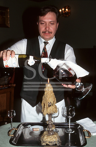 Kracow, Poland. Waiter decanting a bottle of Beaujolais into a glass decanter with a candle in a candlestick with dripped wax.
