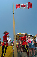 July 1 2002, Montreal, Quebec, Canada<br /> <br /> Two RCMP officiers in Parade Uniform raise the Canadian Flag as while Oh Canada ; the national anthem is sung,during the Canada day celebrations,  July 1st 2001, in the Old-Port of Montreal. <br /> <br /> Mandatory Credit: Photo by Pierre Roussel- Images Distribution. (©) Copyright 2002 by Pierre Roussel <br /> <br /> NOTE l Nikon D-1 jpeg opened with Qimage icc profile, saved in Adobe 1998 RGB. Original file size available in TIFF file.