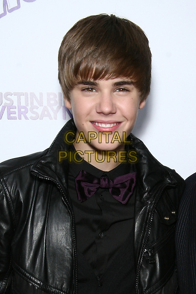 """JUSTIN BIEBER.Special Screening of """"Justin Bieber: Never Say Never"""" at the Regal 42nd Street E-Walk Cinemas, New York, USA, 2nd February 2011..portrait headshot black leather purple bow tie shirt jacket smiling .CAP/LNC/TOM.©LNC/Capital Pictures."""