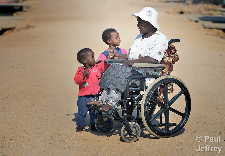 Edith Ncube had polio as a child and today uses a wheelchair in Bulawayo, Zimbabwe, where she visits in the street with neighbor children. Her wheelchair was provided by the Jairos Jiri Association with support from CBM-US.