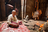 A temple caretaker sits in front of the shrine she has made inside of an ancient temple