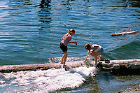 Sointula, Malcolm Island, BC, British Columbia, Canada - Children playing on Log in Water