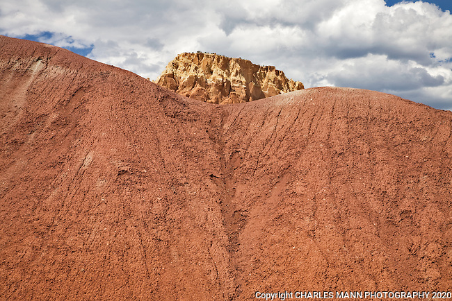 A towering sandstone mesa peeks over the top of a ridge of colored earth at Kitchen Mesa at Ghost Ranch near Abiquiu, New Mexico
