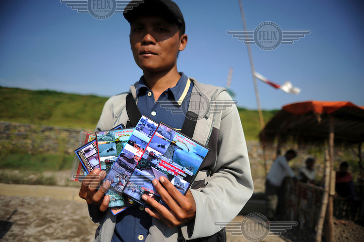 A man who lost his land and job because of the mud flow makes money selling DVDs of the disaster to curious tourists. Since May 2006, more than 10,000 people in the Porong subdistrict of Sidoarjo have been displaced by hot mud flowing from a natural gas well that was being drilled by the oil company Lapindo Brantas. The torrent of mud - up to 125,000 cubic metres per day - continued to flow three years later.