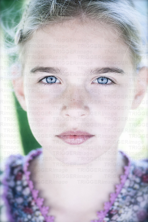 Close up of a young girl with blonde hair and blue eyes looking directly into the camera