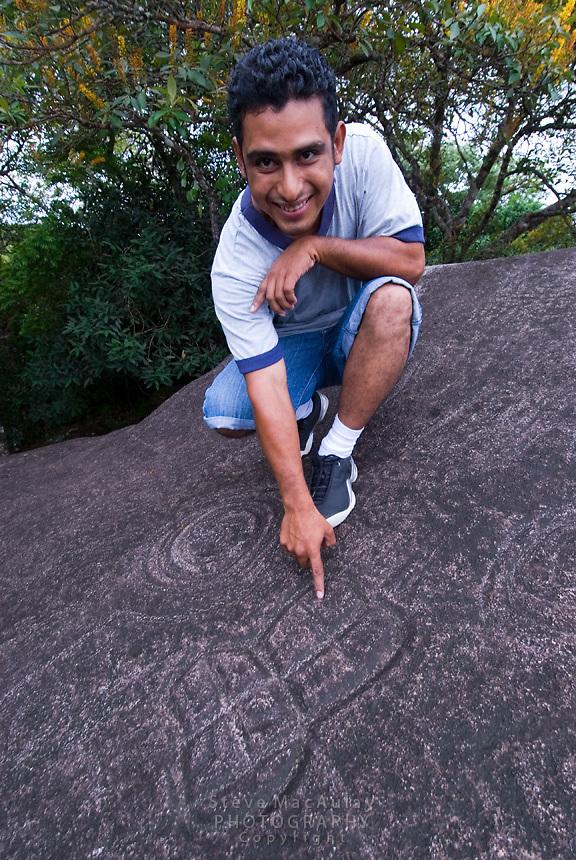 Local guide points out inscriptions, petroglyphs, in rocks, Boquete, Panama,Chiriqui Province