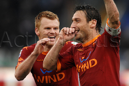 13.03.2011 Francesco Totti scored a free-kick and a penalty to win the Rome derby as Stefan Radu and Cristian Ledesma saw red for Lazio. Picture shows John Arne Riise celebrating with Francesco Totti.