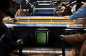 """Workers dye cotton threads for weaving into denim in Zhongshan city, China. .This picture is part of a photo and text story on blue jeans production in China by Justin Jin. .China, the """"factory of the world"""", is now also the major producer for blue jeans. To meet production demand, thousands of workers sweat through the night scrubbing, spraying and tearing trousers to create their rugged look. .At dawn, workers bundle the garment off to another factory for packaging and shipping around the world..The workers are among the 200 million migrant labourers criss-crossing China.looking for a better life, at the same time building their country into a.mighty industrial power."""