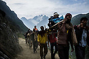 Porters carry hindu pilgrims on the pallanquin along the Amarnath trekking route in Kashmir, India. Hindu pilgrims brave sub zero temperature and high latitude passes and make their pilgrimage to reach the sacred Amarnath cave, which houses a lingam - a stylized phallus, worshiped by Hindus as a symbol of God Shiva. Photo: Sanjit Das/Panos
