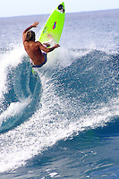 Man doing a cutback on a medium sized wave. Green surfboard.