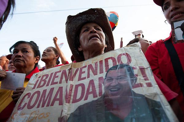 """CAR107 CARACAS (VENEZUELA) 18/02/2013.- Un grupo de seguidores del presidente de Venezuela, Hugo Chávez, muestran su apoyo al mandatario en la entrada del Hospital Militar Dr Carlos Arvelo, en Caracas, hoy, lunes 18 de febrero de 2013, a donde llegó en horas de la madrugada. Con euforia y al grito de """"¡Volvió!"""", el chavismo dio la bienvenida a su líder, luego de haber estado más de dos meses hospitalizado en Cuba sin dejarse ver. EFE/MIGUEL GUTIÉRREZ.."""