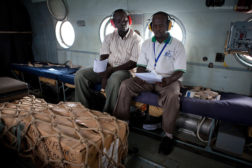 11 december 2010 - Riwoto, South Sudan - Lochebe Boniface Losike and Lopeta Philemon Lokai (R), training officers for the Southern Sudan Referendum Comission sit near completed registration materials inside a UNMIS helicopter in Riwoto, Southern Sudan. the UNMIS retrieves completed registration materials in Riwoto - Kapoeta North County, the day after registration for South Sudan's referendum closed. The referendum is scheduled to take place on Jan. 9 2010. Photo credit: Benedicte Desrus