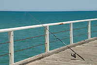 A fishing rod propped against the rails at Henley Jetty while a fisherman awaits a nibble, Henely Beach, Adelaide, South Australia