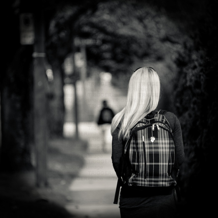 A girl with long blonde hair and a plaid backpack walking down a neighbourhood sidewalk with a blurred man in the distance.