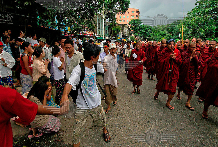 Bystanders line the streets to show their solidarity with protesting Buddhist monks calling for the overthrow of the country's military junta. Their anxiety about the safety of the protesters is palpable. Thousands took to the streets again despite a new threat that the military would shoot on sight any gatherings of over four people.