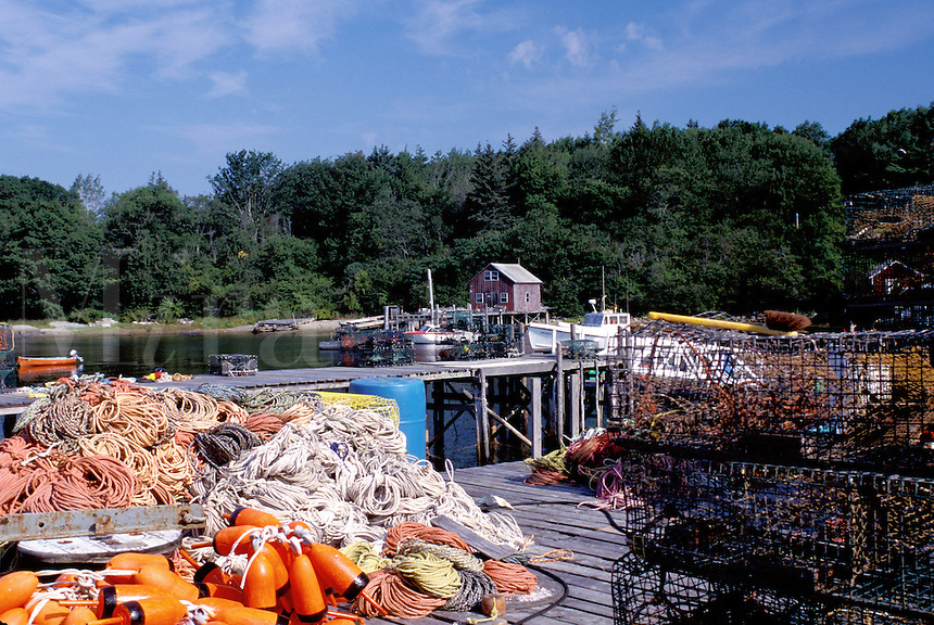New Harbor, Maine, ME, Pemaquid, Fishing nets, lobster traps and buoys on a dock in the harbor.
