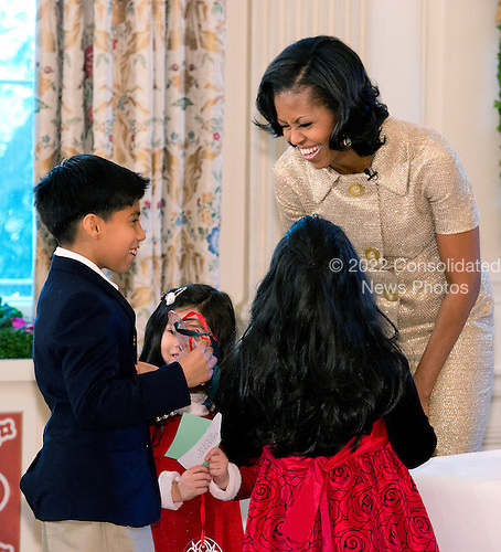 First lady Michelle Obama helps children with a crafts project during the press preview of the 2012 White House Christmas decorations in Washington, DC on Wednesday, November 28, 2012..Credit: Ron Sachs / CNP