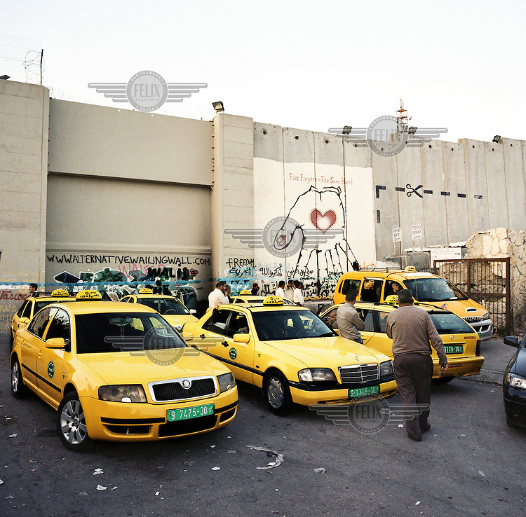 Taxis waiting for customers as they come through a check point in the separation barrier near Bethlehem.