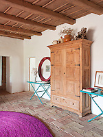 A pair of bright turquoise console tables flank a large wooden free-standing cupboard in the entrance hall