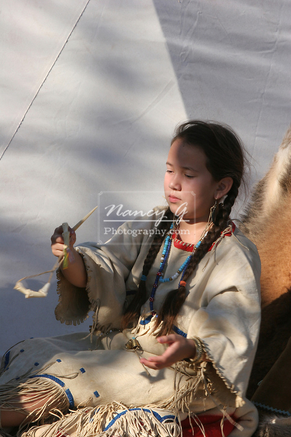 A young Native American Indian child playing with native primitive toys
