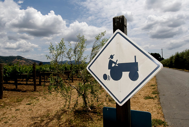 Sign near vineyard in Rutherford, Ca., displays tractor image.