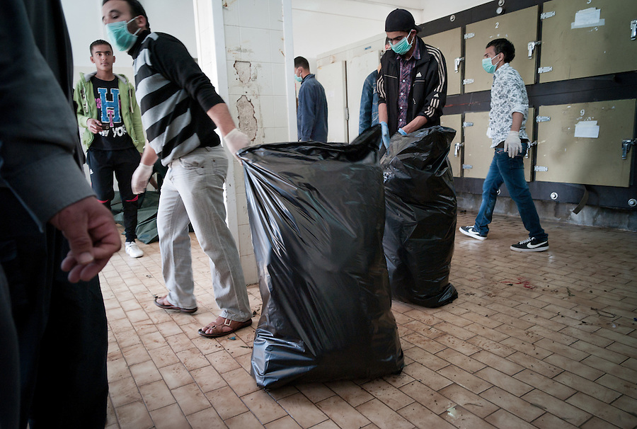 Bagged up body parts of suspected Gaddafi being dragged away in Benghazi, Libya.
