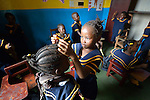 One girl helps another with her braid in a day care center in Monrovia, Liberia, sponsored by United Methodist Women.