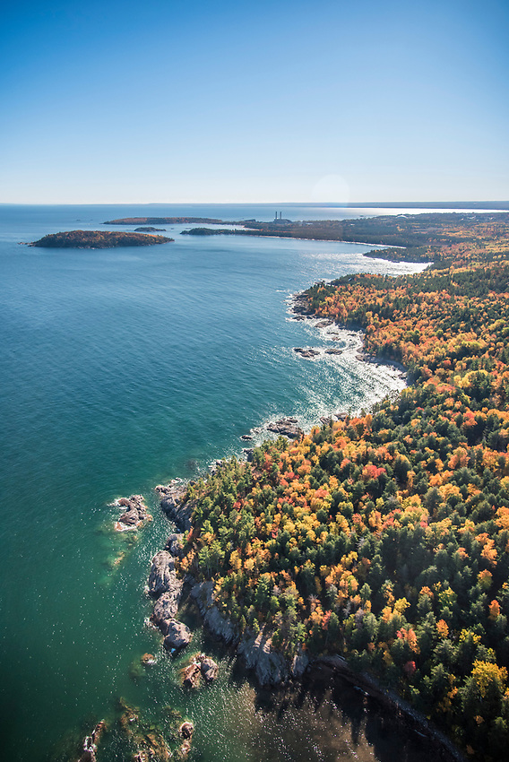 Aerial photography of  the rugged Lake Superior shoreline north of Marquette, Michigan looking south towards Marquette, during fall color season.