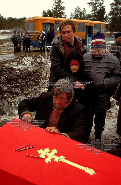 © Paul Lowe / Panos Pictures..Semipalatinsk, KAZAKHSTAN. ..Funeral of Elena Dolina who died of stomach cancer aged 38.  Her son Yevgeny, in the backgroudn is dying from Leukemia.  Her father, Vasily Dolin, on the boy's left, was an agricultural worker on the test site in the 1950's, and suffers from mouth cancer...On 29th August 1949 the first Russian plutonium bomb was exploded at the Semipalatinsk nuclear test site, which came to be known as 'The Polygon'. This first detonation was followed by more than 500 nuclear explosions, both atmospheric and underground..The effects in the Semipalatinsk region have been devastating. According to the UN more than 1.2 million people have been contaminated or are living in severely contaminated areas. Of these over 100,000 suffer from radiation related diseases. Even though testing stopped in 1989 the situation is continuing to deteriorate. Two out of every three children born in the region suffer from genetic defects.