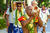 A Hawaiian conch shell blower in Waikiki, wearing a yellow and orange replica of a feathered cape, as well as plumeria and maile leaf lei, leads a parade of lei draped surfboards in honor of legendary surfer Duke Kahanamoku 's birthday. Conch shells