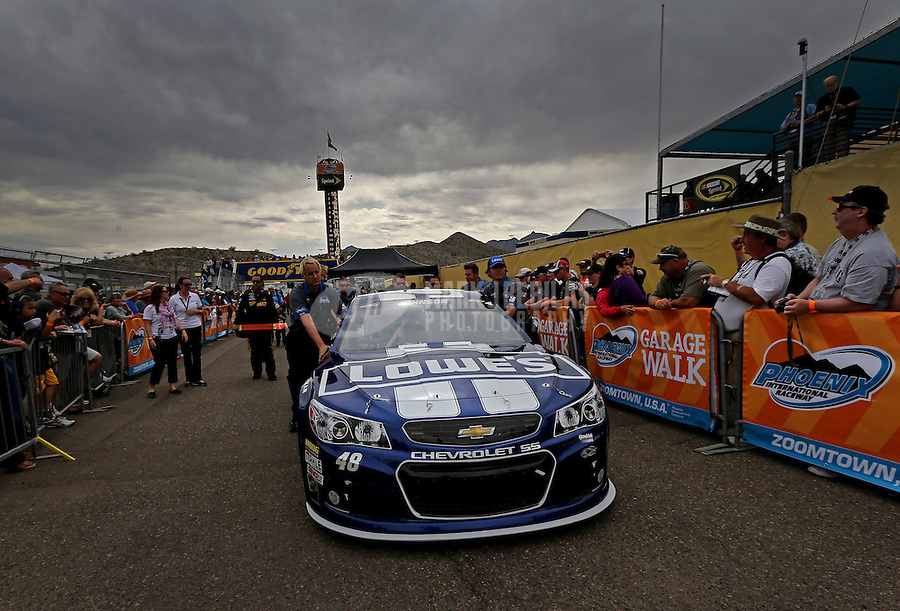 Mar. 3, 2013; Avondale, AZ, USA; Crew members push the car of NASCAR Sprint Cup Series driver Jimmie Johnson through tech inspection prior to the Subway Fresh Fit 500 at Phoenix International Raceway. Mandatory Credit: Mark J. Rebilas-