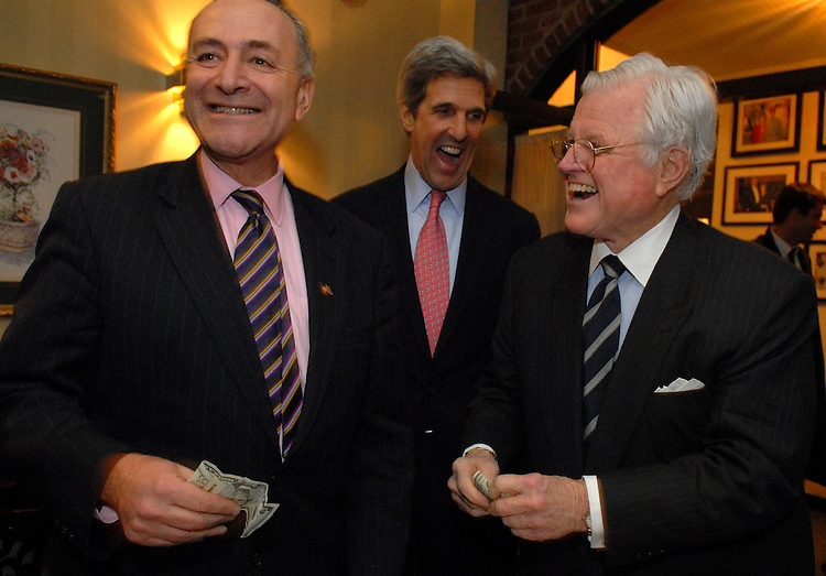 "Sen. Chuck Schumer, D-N.Y., left, gets money for his new book ""Positively American"" from Sen. Ted Kennedy, D-Mass., right, as Sen. John Kerry, D-Mass., looks on, at a book signing reception at the Hunan Dynasty on Capitol Hill, Tuesday, January 30, 2007."
