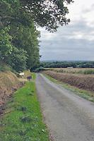 Sur une petite petite route, en pleine campagne, apparait un panneau indiquant l'entree du parking