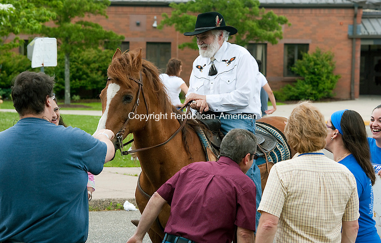 TORRINGTON, CT-061814JS01--Torrington Middle School teacher Matthew Valenti, who is retiring after 40 years, says goodbye to fellow staff members as he prepares to ride off on his horse Calypso Jack on the last day of school on Wednesday. <br />  Jim Shannon Republican-American
