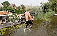 Nederland  Schermerhorn 2016 07 10.  Jaarlijkse Prutmarathon door de modderige slootjes van de Mijzenpolder. Man springt na afloop van een brug, om zich schoon te spoelen.  Foto Berlinda van Dam / Hollandse Hoogte
