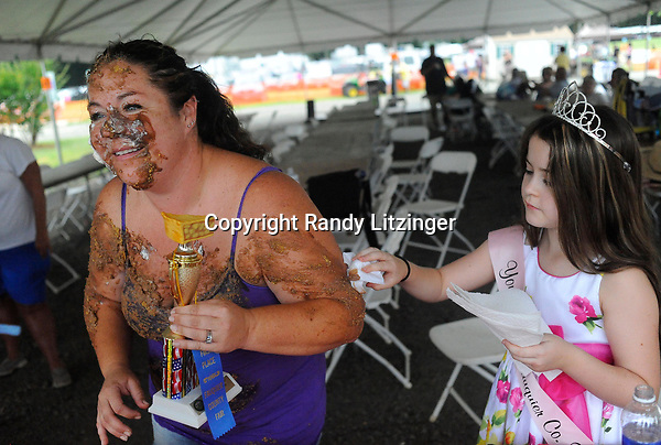 Daughter and Fair Princess, Mikayla Pompell (at right) daintily wipes the chocolate pie off of her mom Tiffany after her mom won the pie eating contest at the county fair.