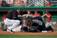 Batavia Muckdogs manager Tom Lawless (10) and athletic trainer Jordan Wheat checks on Brayan Hernandez (23) after getting hit in the face by a pitch during a NY-Penn League game against the State College Spikes on July 2, 2019 at Dwyer Stadium in Batavia, New York.  Batavia defeated State College 1-0.  (Mike Janes/Four Seam Images)