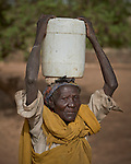 A woman carries water in Gidel, a village in the Nuba Mountains of Sudan. The area is controlled by the Sudan People's Liberation Movement-North, and frequently attacked by the military of Sudan. The Catholic Church has drilled wells and sponsored schools and health care facilities throughout the war-torn region.